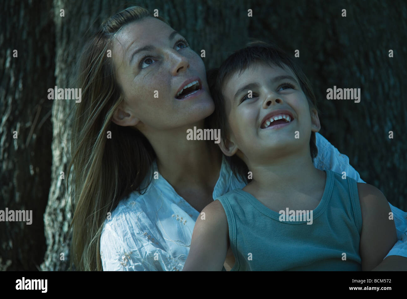 Mother sitting beneath tree with son in lap, both looking up - Stock Image