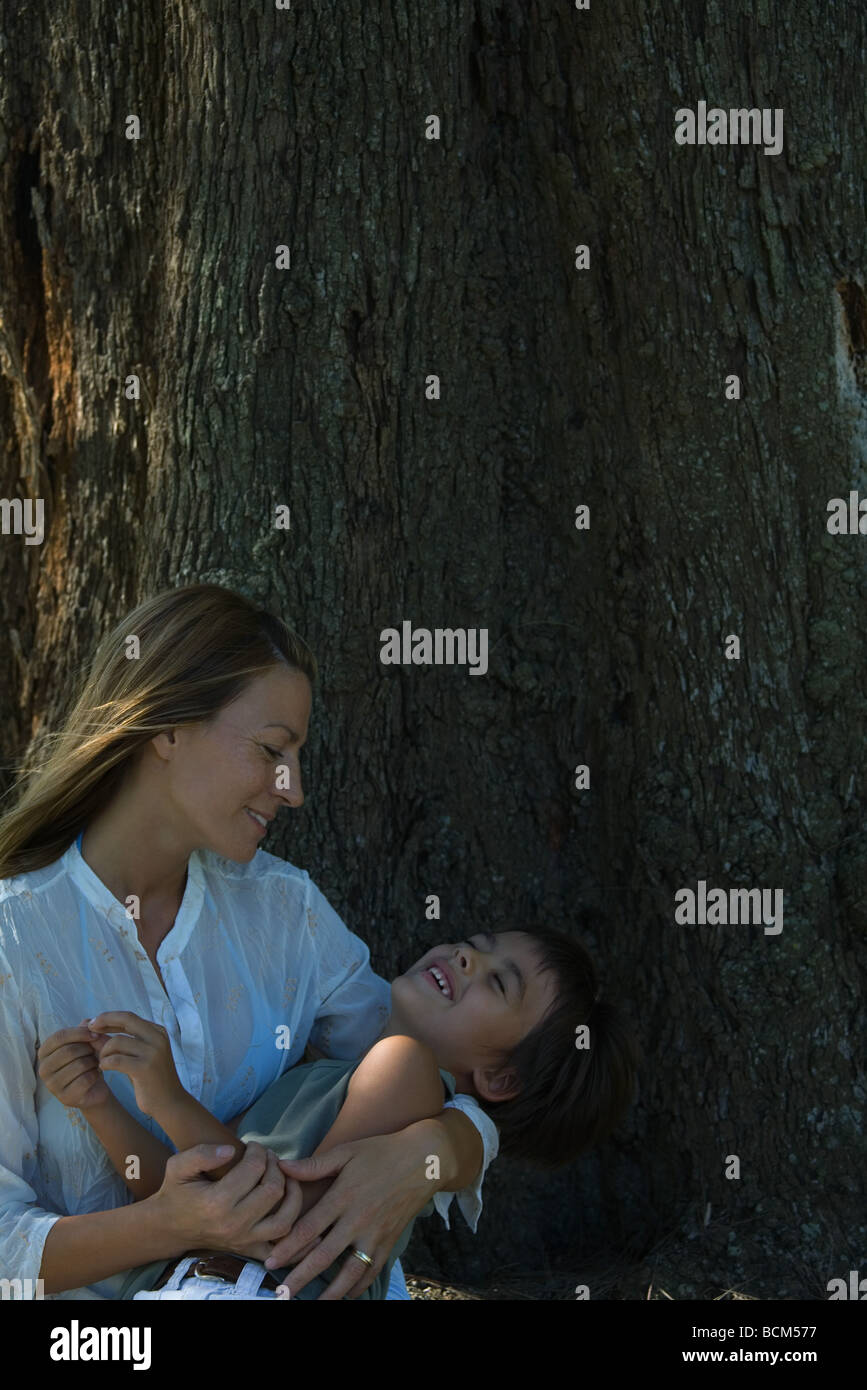 Mother holding son beneath tree, boy's eyes closed - Stock Image