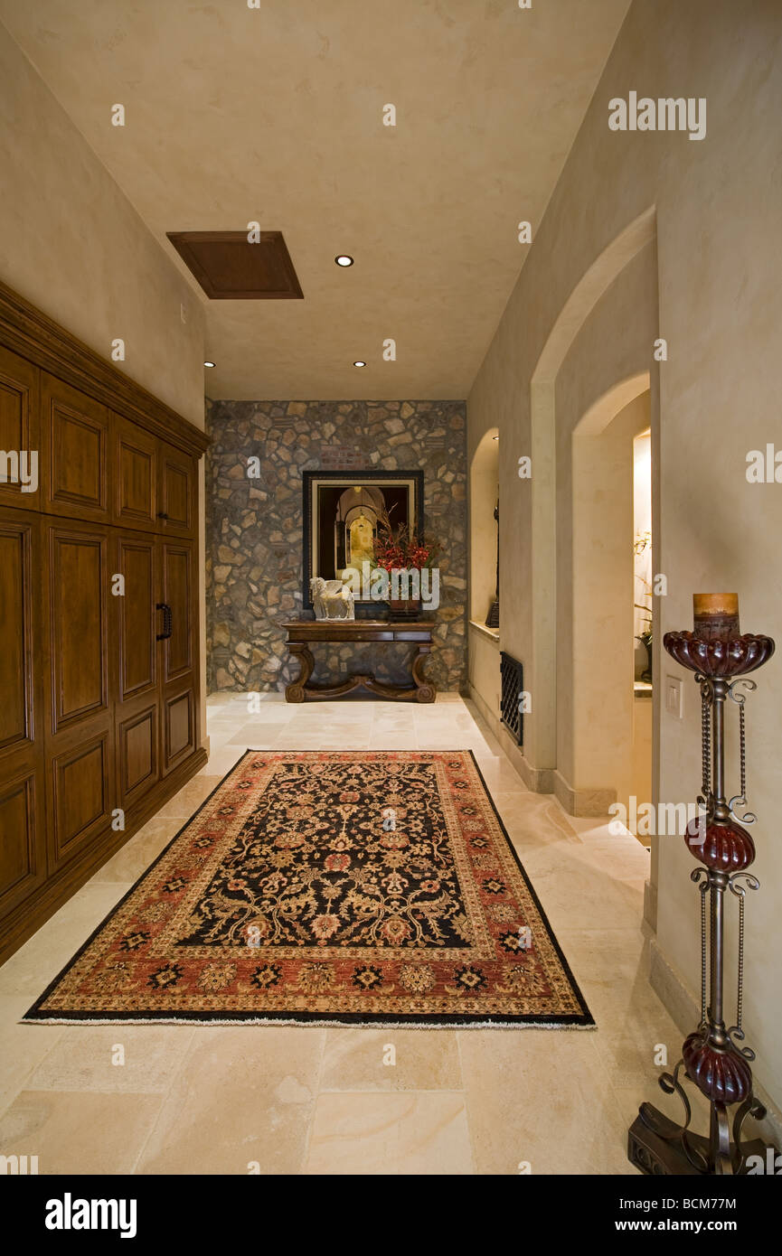 Hallway shows wooden cabinets on left and tall candle stick on right and portrait on stone wall - Stock Image