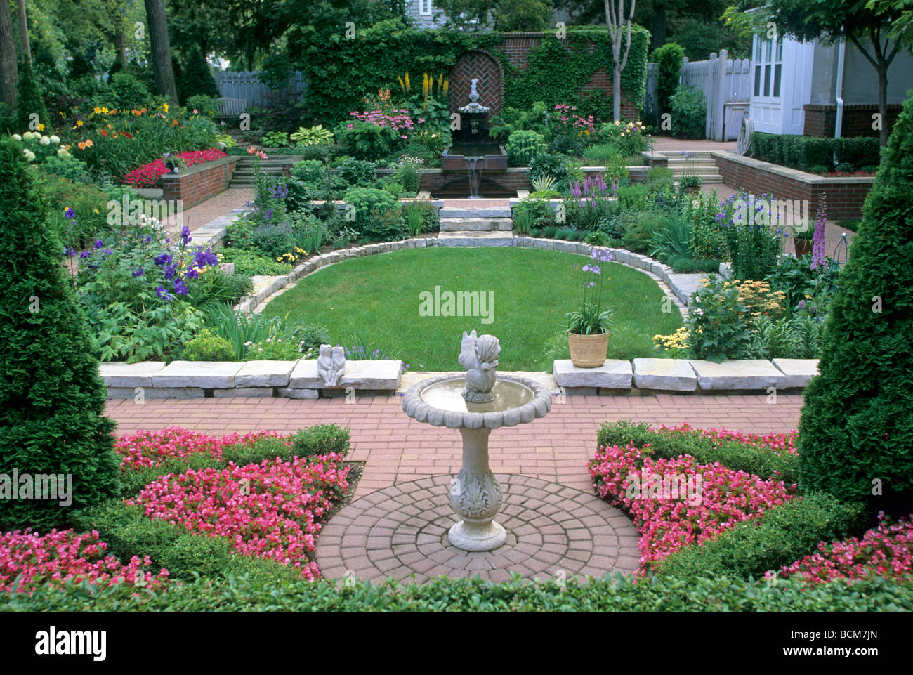 FORMAL GARDEN IN MINNEAPOLIS, MINNESOTA. BEGONIAS, BOXWOOD, ARBORVITAE AND A MIXTURE OF PERENNIALS.  SUMMER. Stock Photo