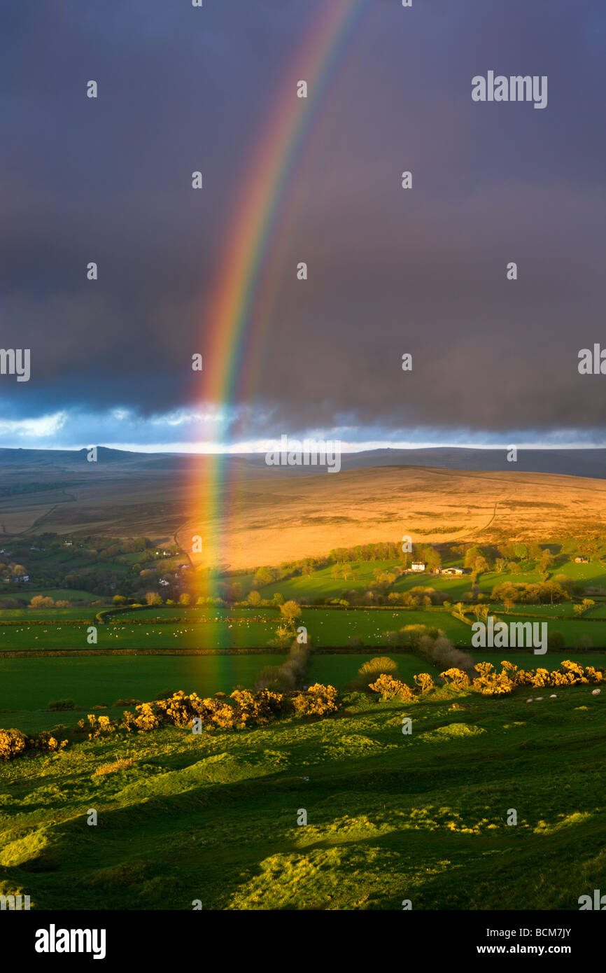 Rainbow above rolling farmland on the edges of Dartmoor National Park Devon England Spring April 2009 Stock Photo