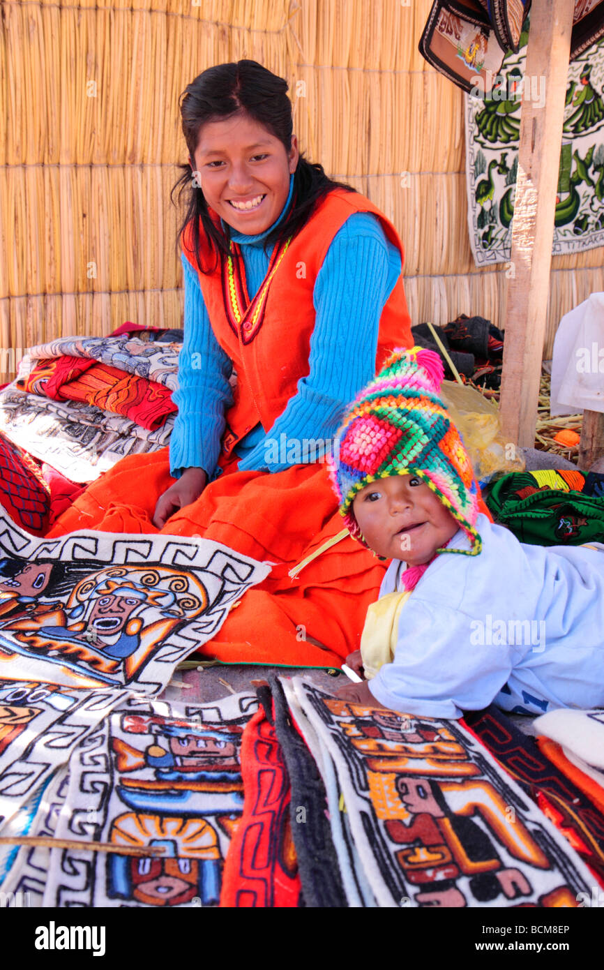 portrait of a woman selling souvenirs and her young child, Uro Island, Lake Titicaca, Puno, Peru - Stock Image