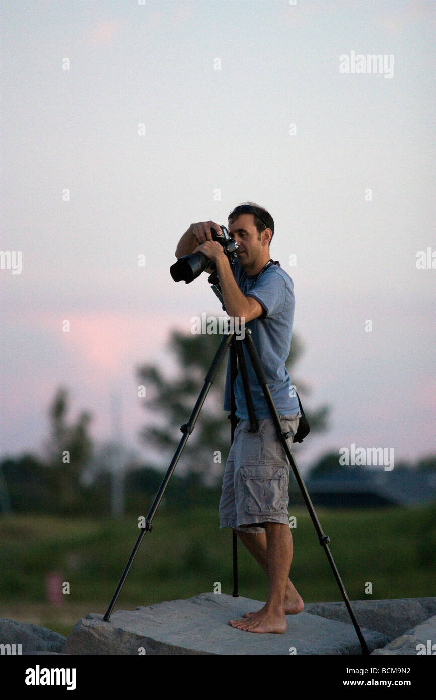 A barefoot photographer on a rock at sunset - Stock Image