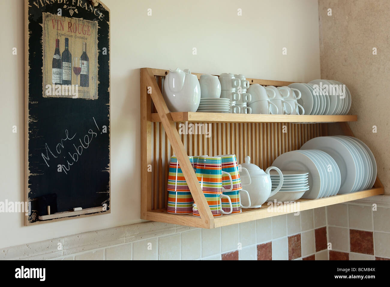 Close-up of notice-board on wall beside wooden plate-rack with striped cups and white plates & Close-up of notice-board on wall beside wooden plate-rack with Stock ...