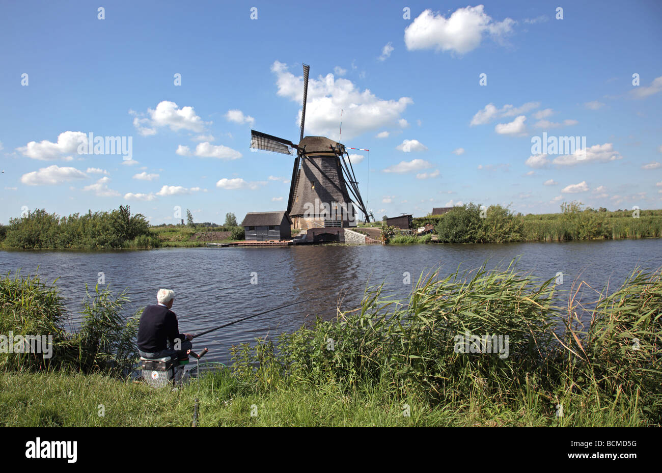 old top-wheeler windmill at Kinderdijk with fisherman fishing at the canal Netherlands Europe - Stock Image