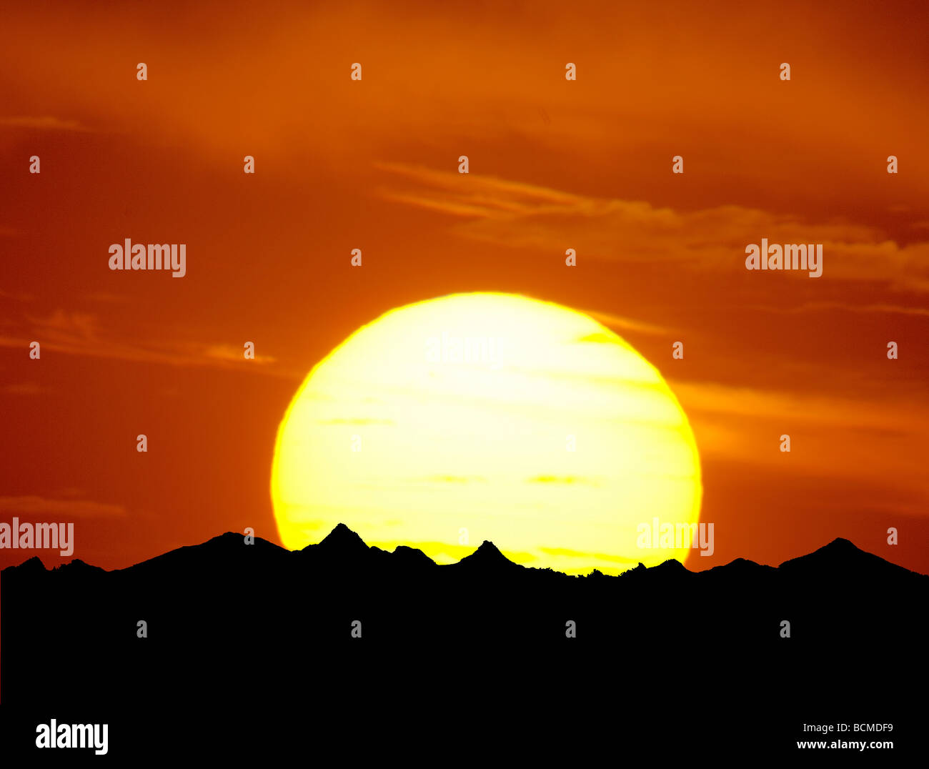 telephoto photograph of large sunset and mountains - Stock Image