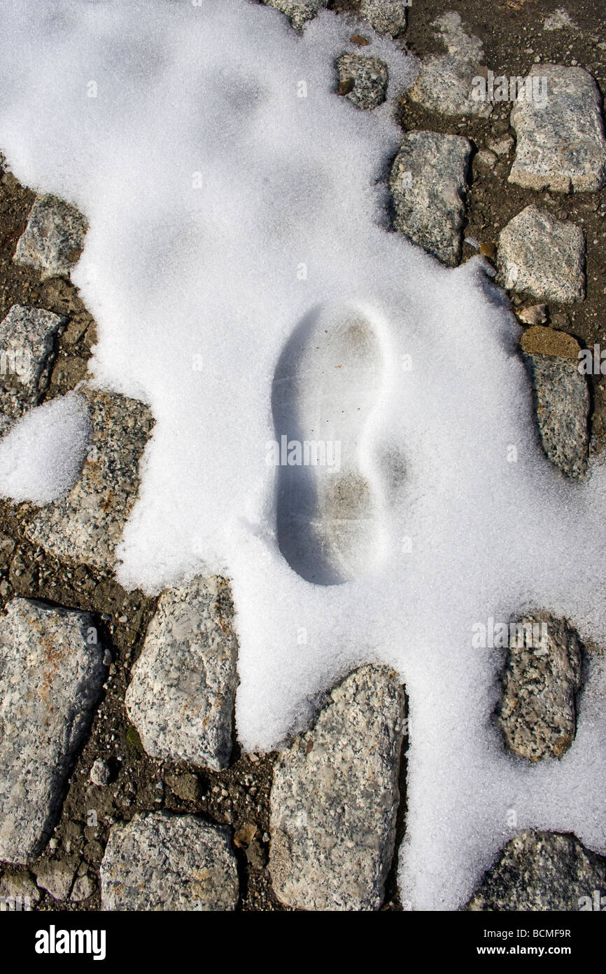 Footprint in snow on cobblestone street - Stock Image