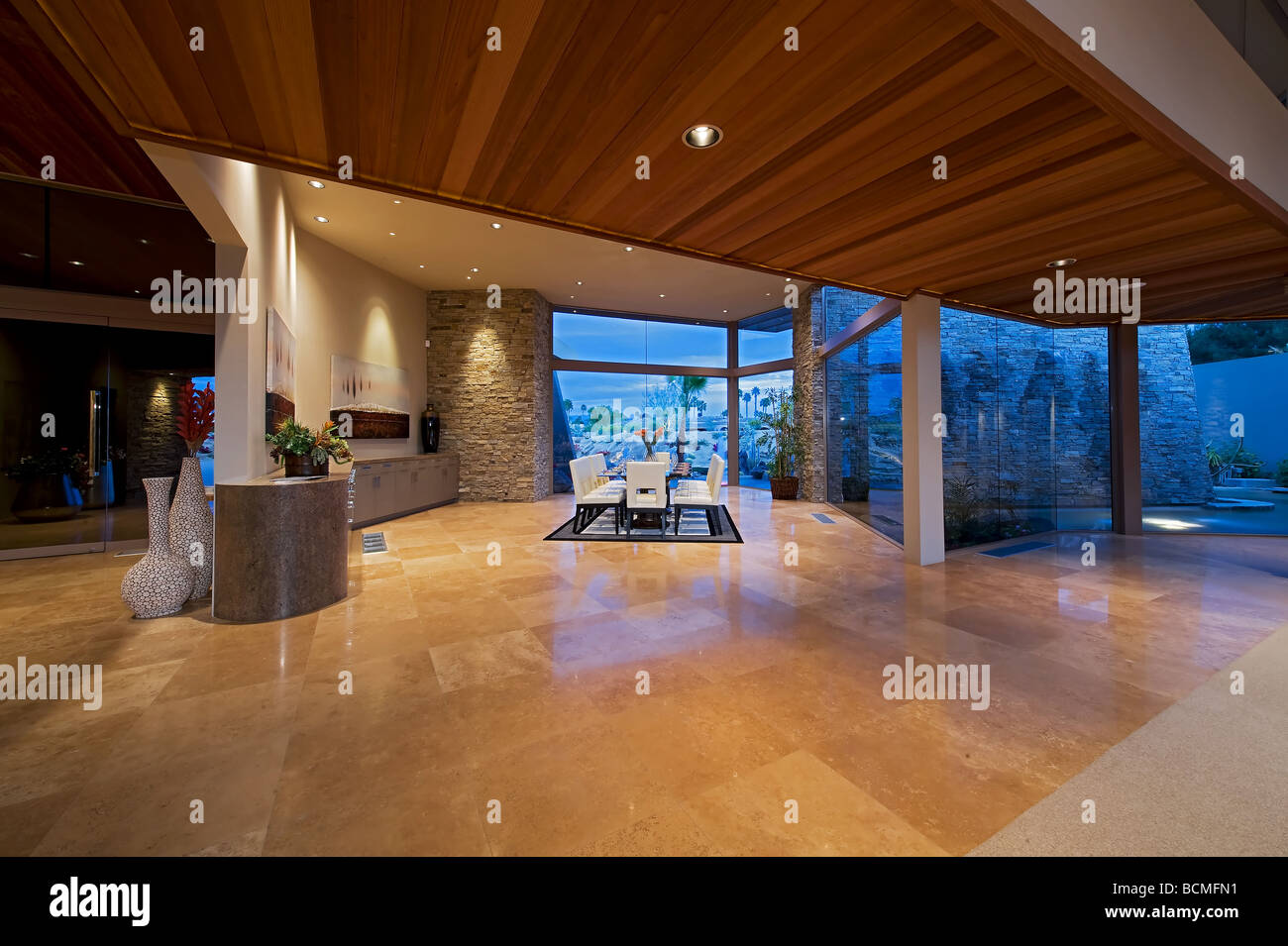 Distant view of ultra modern large dining room with glass walls - Stock Image