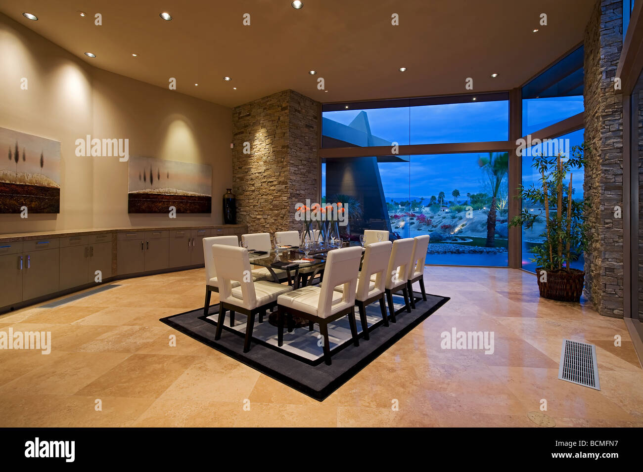 Spectacular modern dining room featuring stacked stone walls and white leather dining chairs - Stock Image
