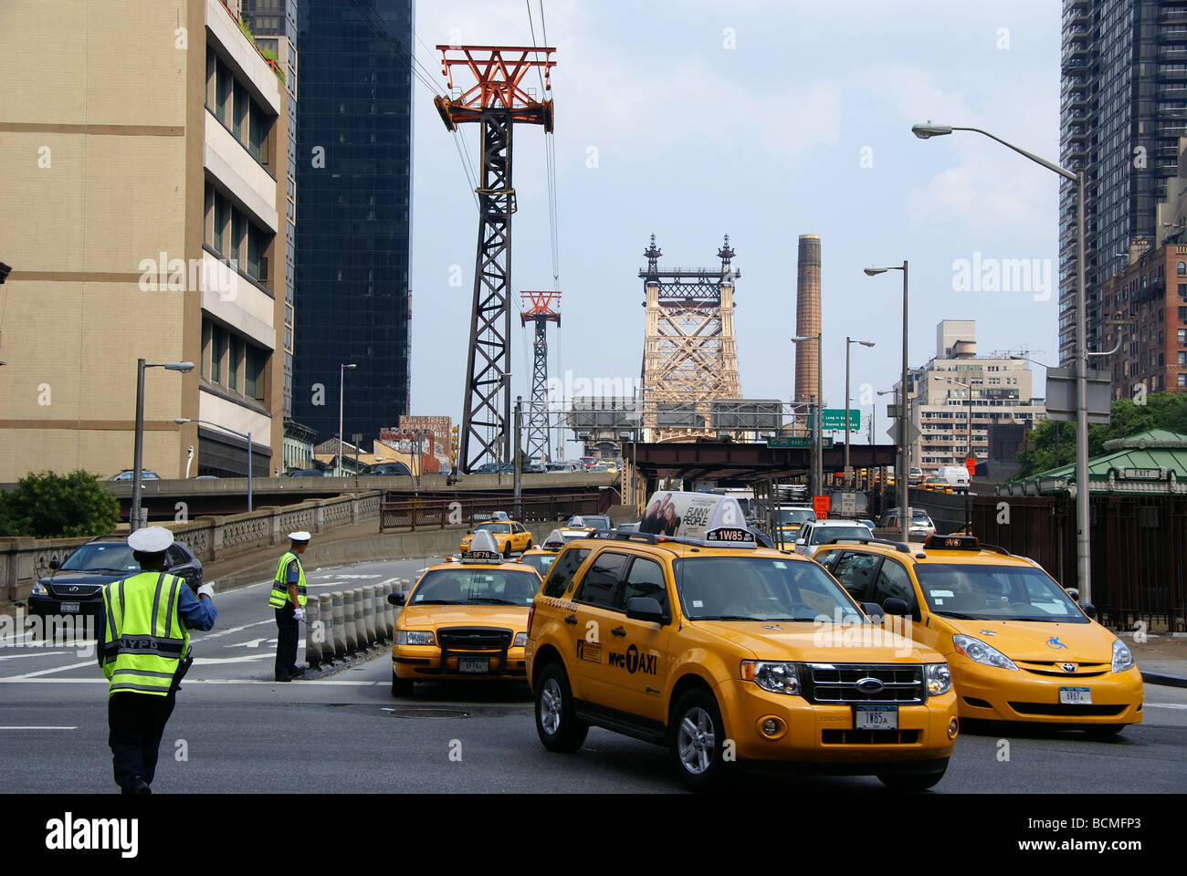 Police officers direct traffic in Manhattan by Roosevelt Island tramway station - Stock Image