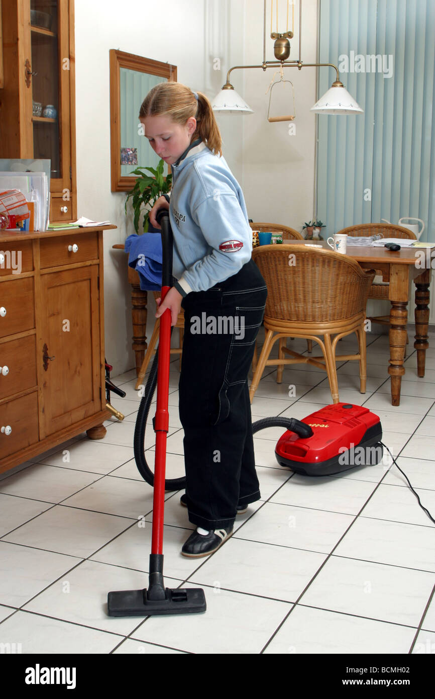 Young girl helping in household, as the young girl is cleaning the floor with vacuum cleaner - Stock Image