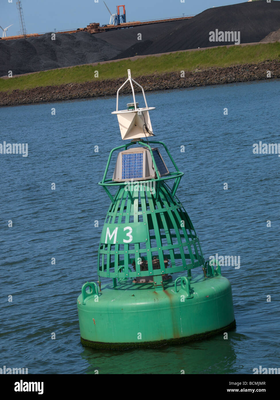 Modern green buoy in the port of Rotterdam marking the shipping lane with solar panels to power its transmitter - Stock Image