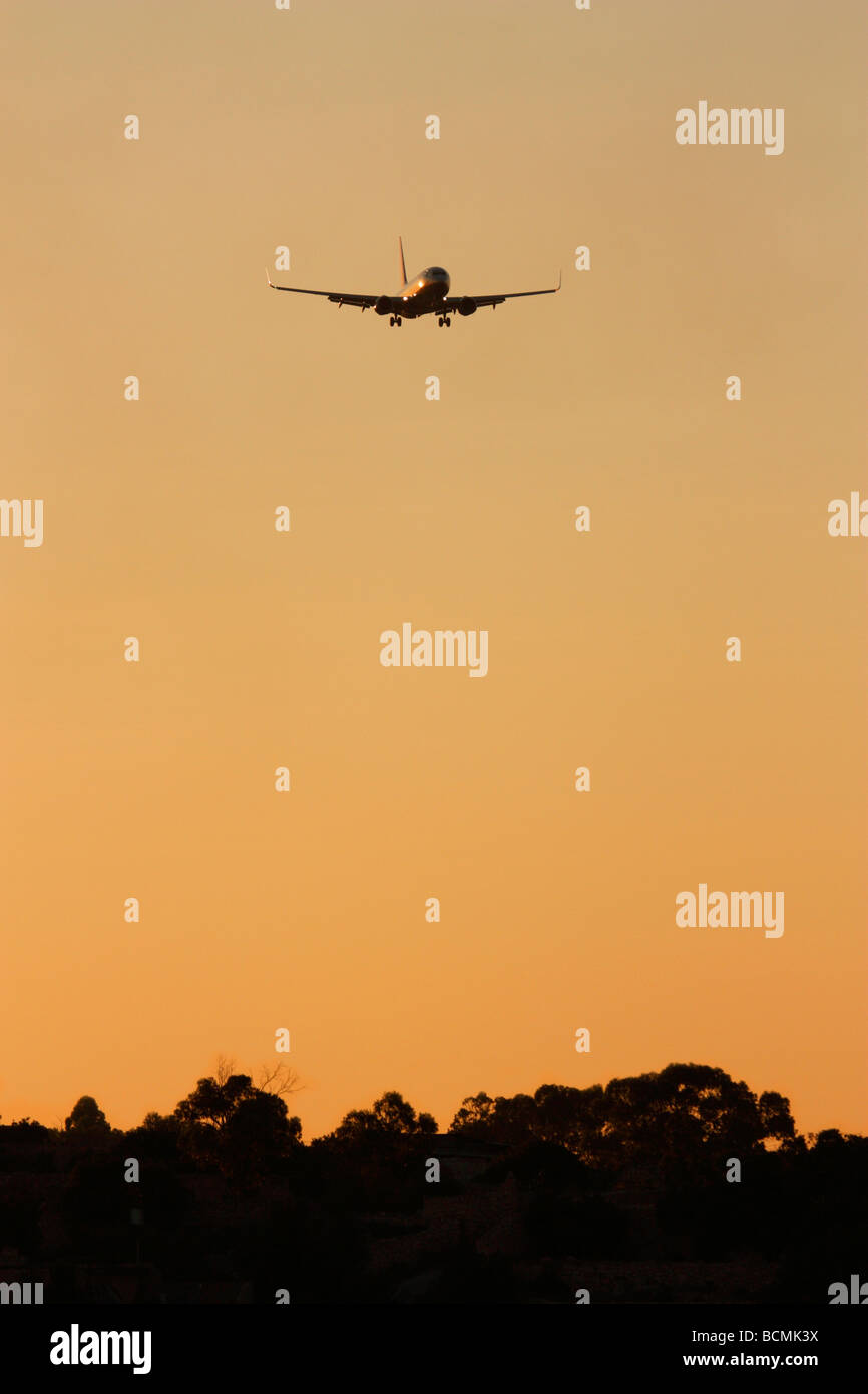 Commercial aviation, air travel and the environment. Boeing 737-800 airliner flying over trees at sunset. No proprietary - Stock Image