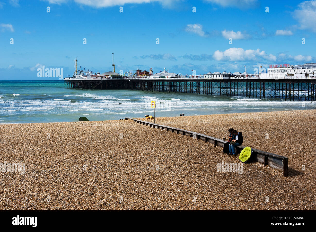 Two people sitting on a breakwater on the shingle beach near the pier at Brighton in Sussex. - Stock Image