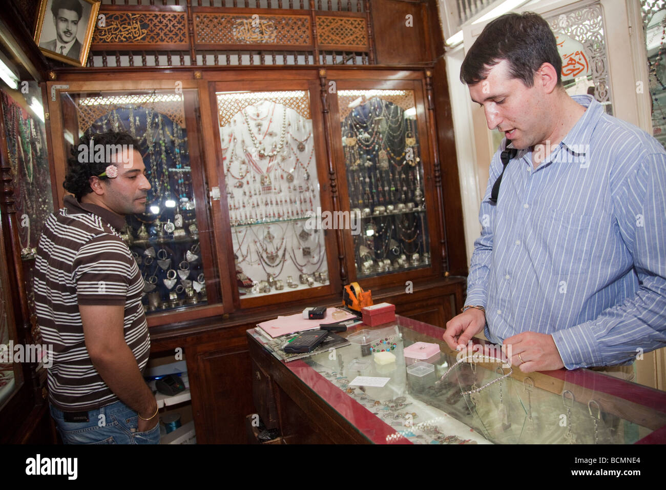 An American tourist buys a silver necklace in a jewelry store in the Tunis Medina (old city). - Stock Image