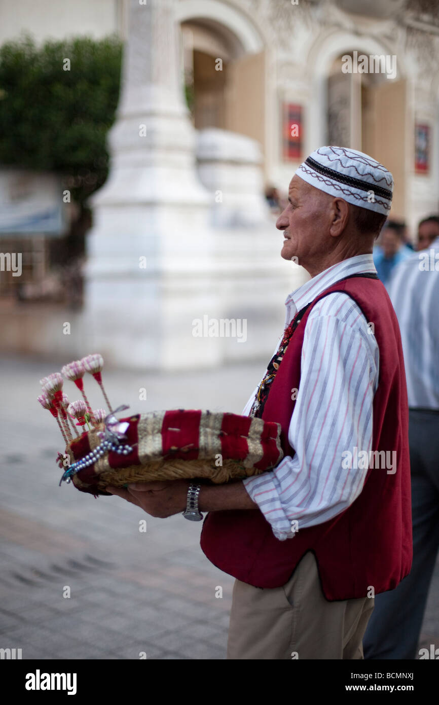 A man sells jasmine flowers in front of the Theatre Municipal in Tunis, Tunisia. - Stock Image