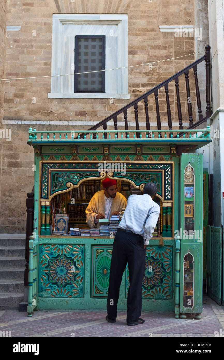 A man browses the offerings of a bookseller next to the Jemaa Zitouna (Great Mosque) deep in the Tunis Medina (Tunisia). - Stock Image