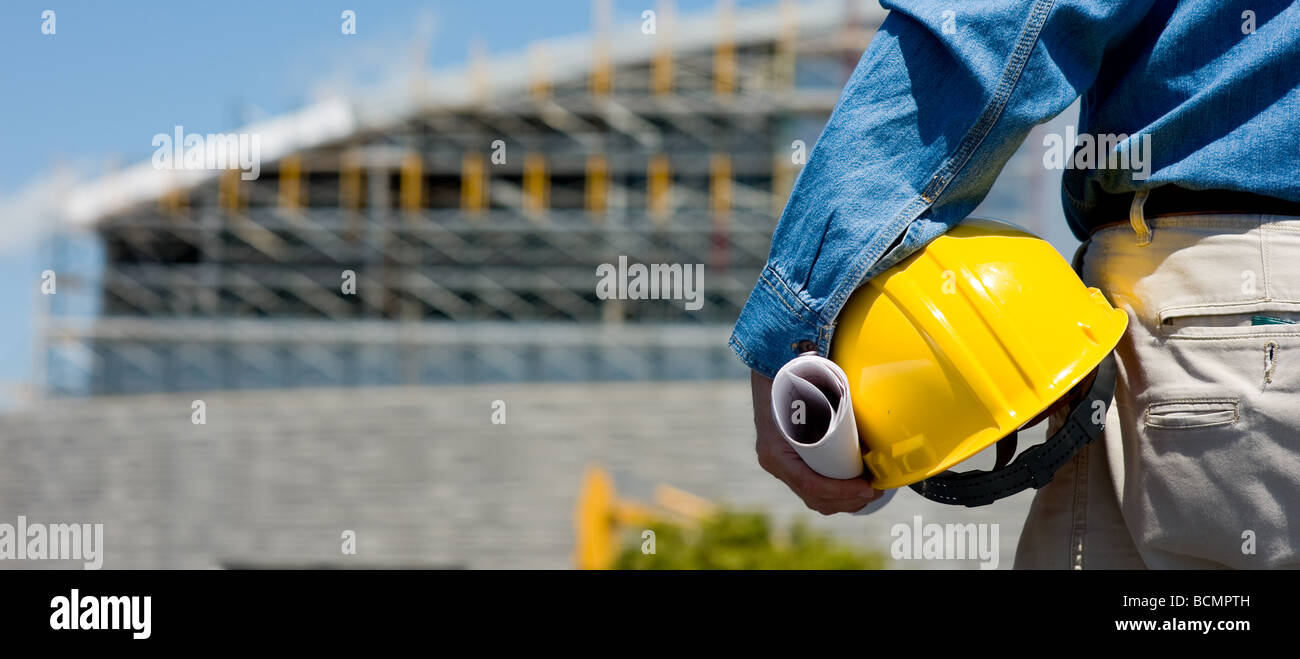 A construction worker or foreman at a construction site observing the progress of construction job or project with - Stock Image