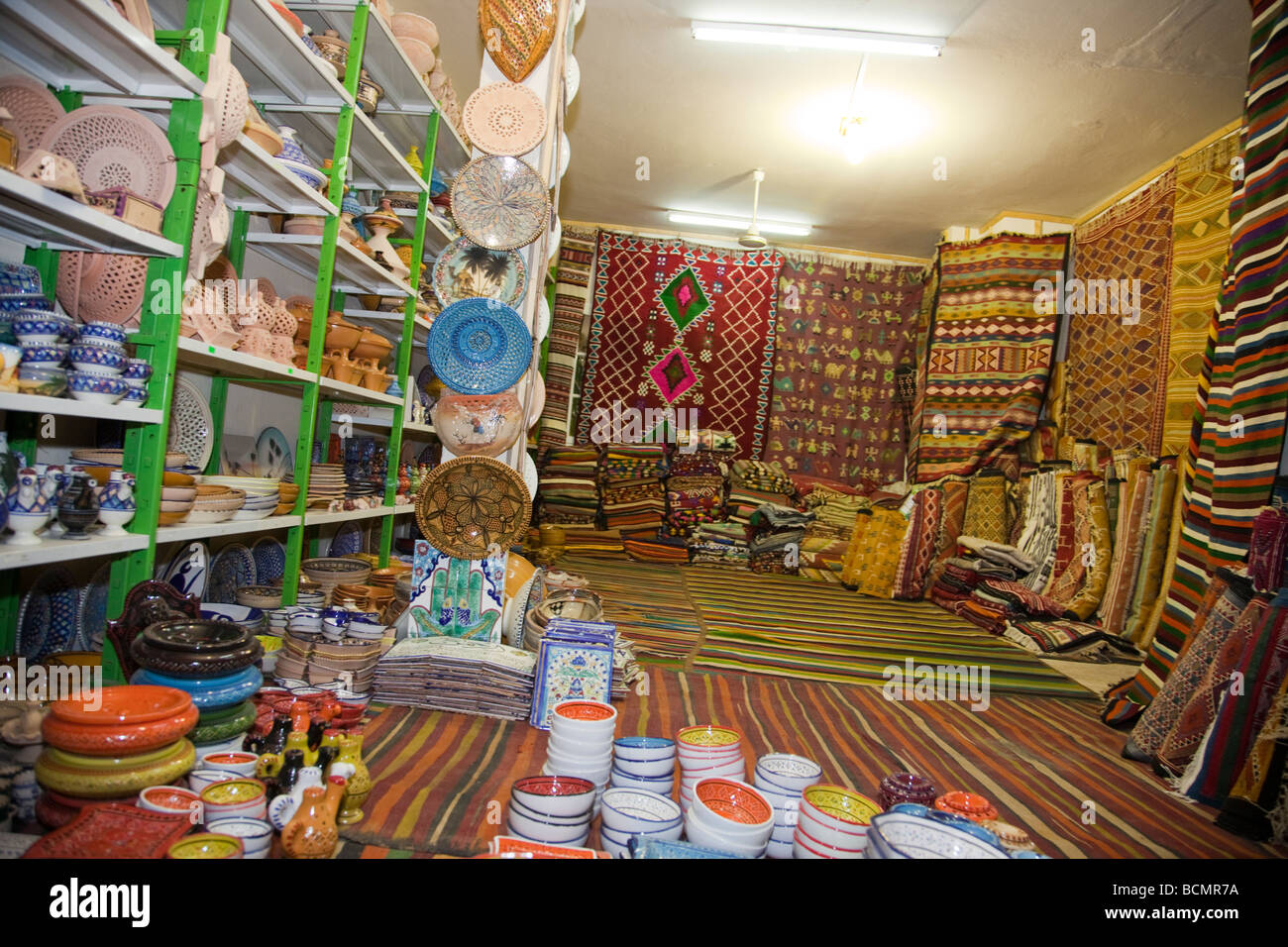 A shop in Tozeur, Tunisia sells rugs, clothing, and other traditional handicrafts to tourists. - Stock Image