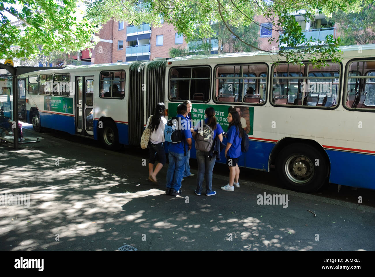 Schoolchildren chat next to an old bendy bus. - Stock Image