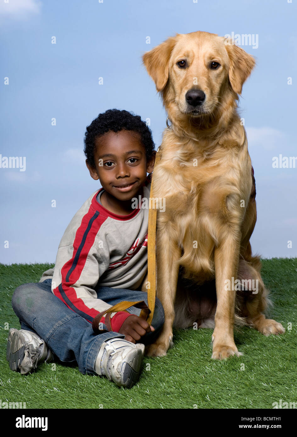 African American boy and a Golden Retriever sitting on the grass, 1 year old, against a blue sky, studio shot - Stock Image