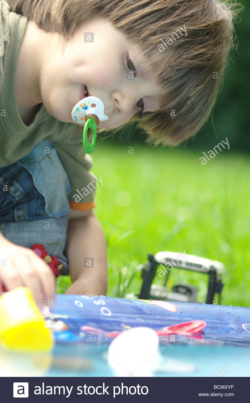 Child little boy CLOSE UP playing with toys in the garden Stock Photo