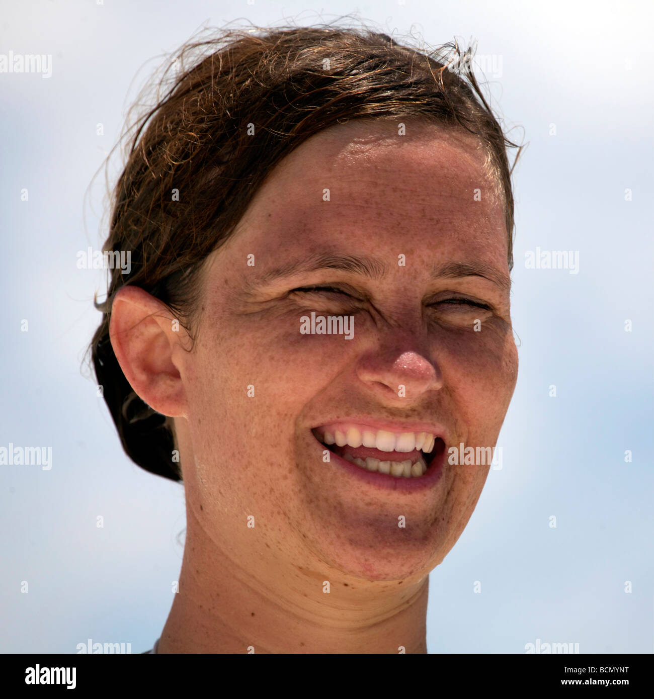Smiling girl outdoors wet dishevelled hair freckles early twenties Nancia fresh faced - Stock Image