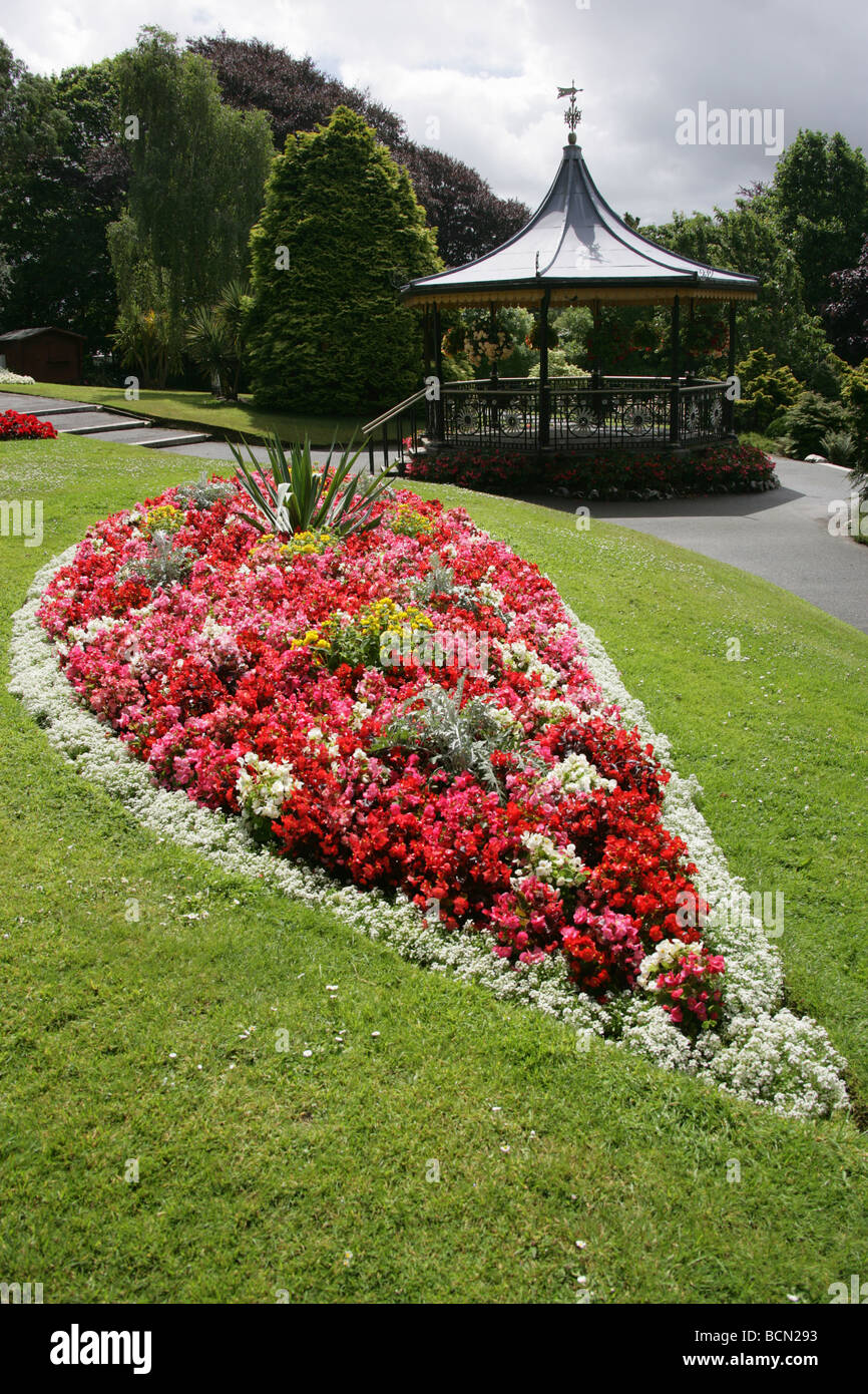 City of Truro, England. Flower beds in full bloom in Truro's Victoria Gardens, with the Victorian bandstand in the Stock Photo