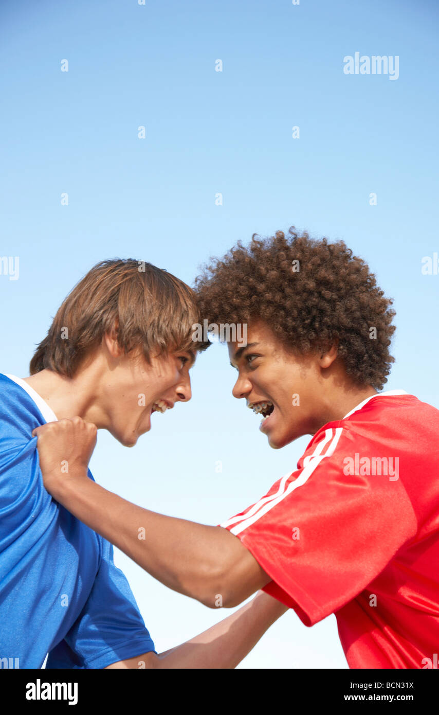 Two opposing team members screaming at each other, foreheads touching - Stock Image