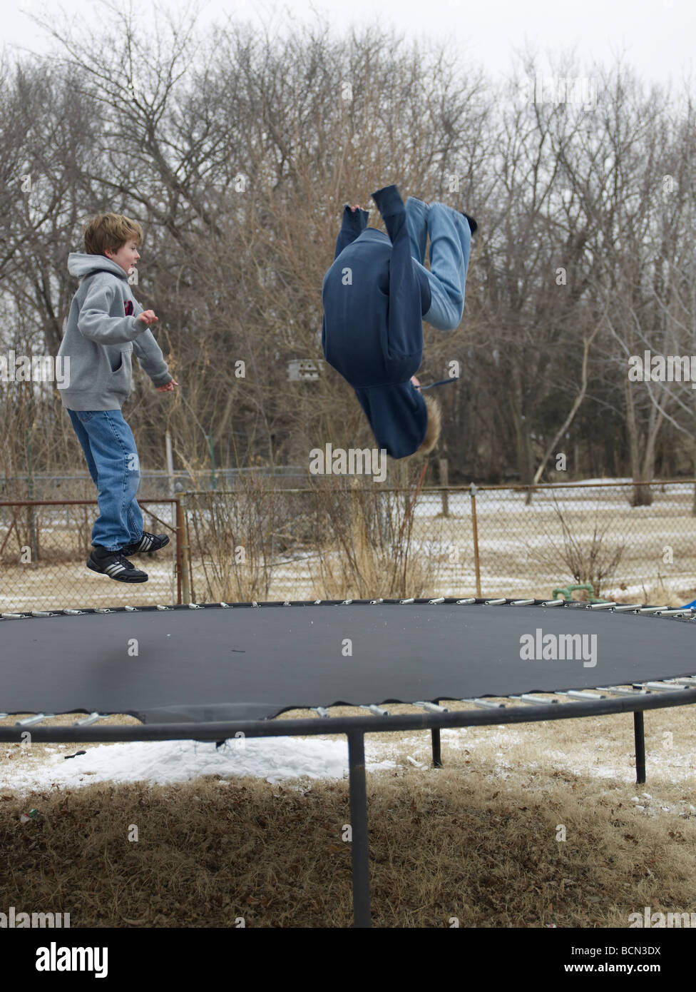 Two Children Jumping on Trampoline Stock Photo