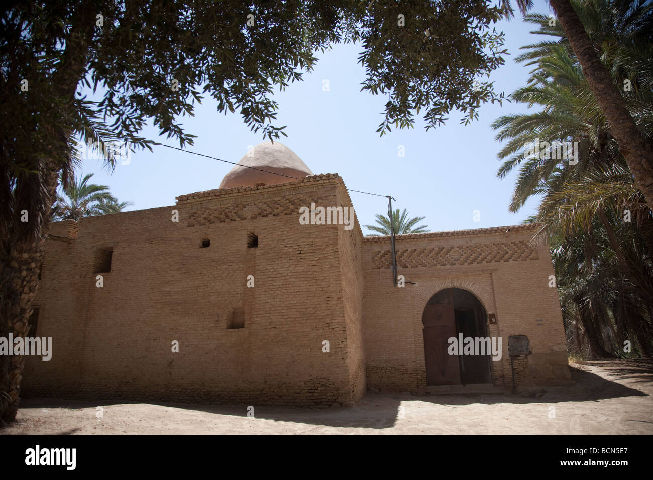 A mosque in the Tozeur oasis displays the traditional and unique brickwork of Tozeur, Tunisia. - Stock Image