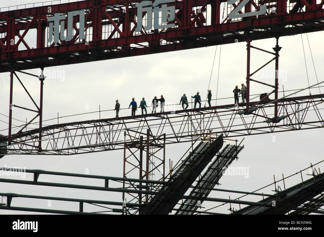 Construction workers standing on the scaffold, Shanghai, China - Stock Image