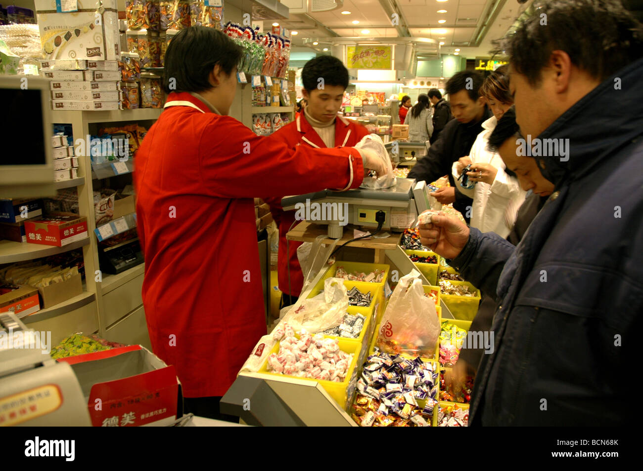 People buying Shanghai local specialty in Shanghai First Food Mall on Nanjing Road, Shanghai, China - Stock Image