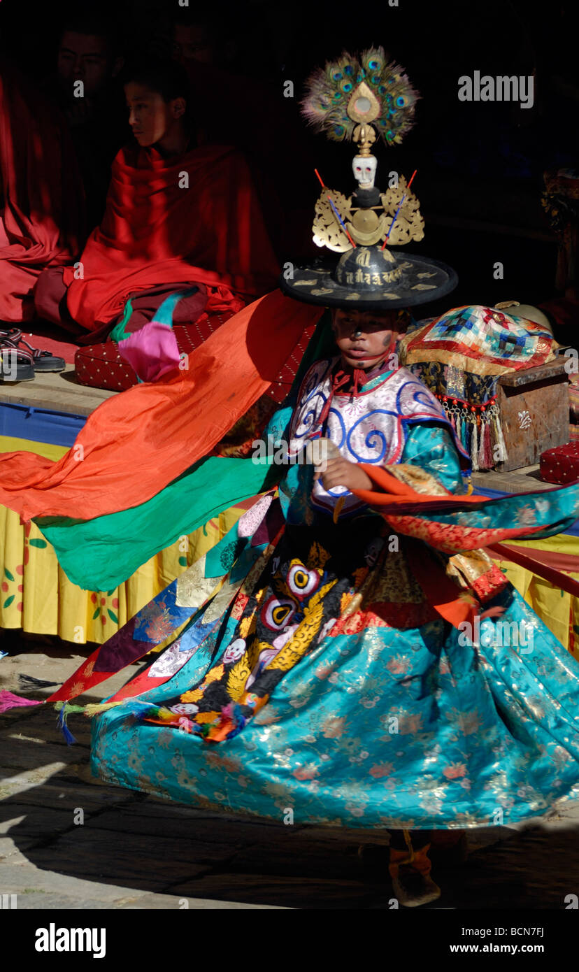 A black hat dancer dressed in gorgeous silk robes spins across the courtyard of Mongar Dzong. Stock Photo