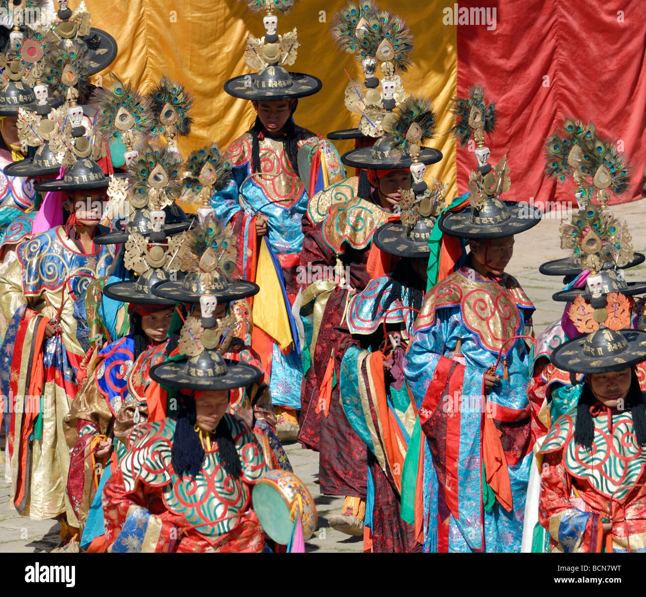 Black hat dancers dressed in gorgeous silk robes parade into  the courtyard of Mongar Dzong. Stock Photo