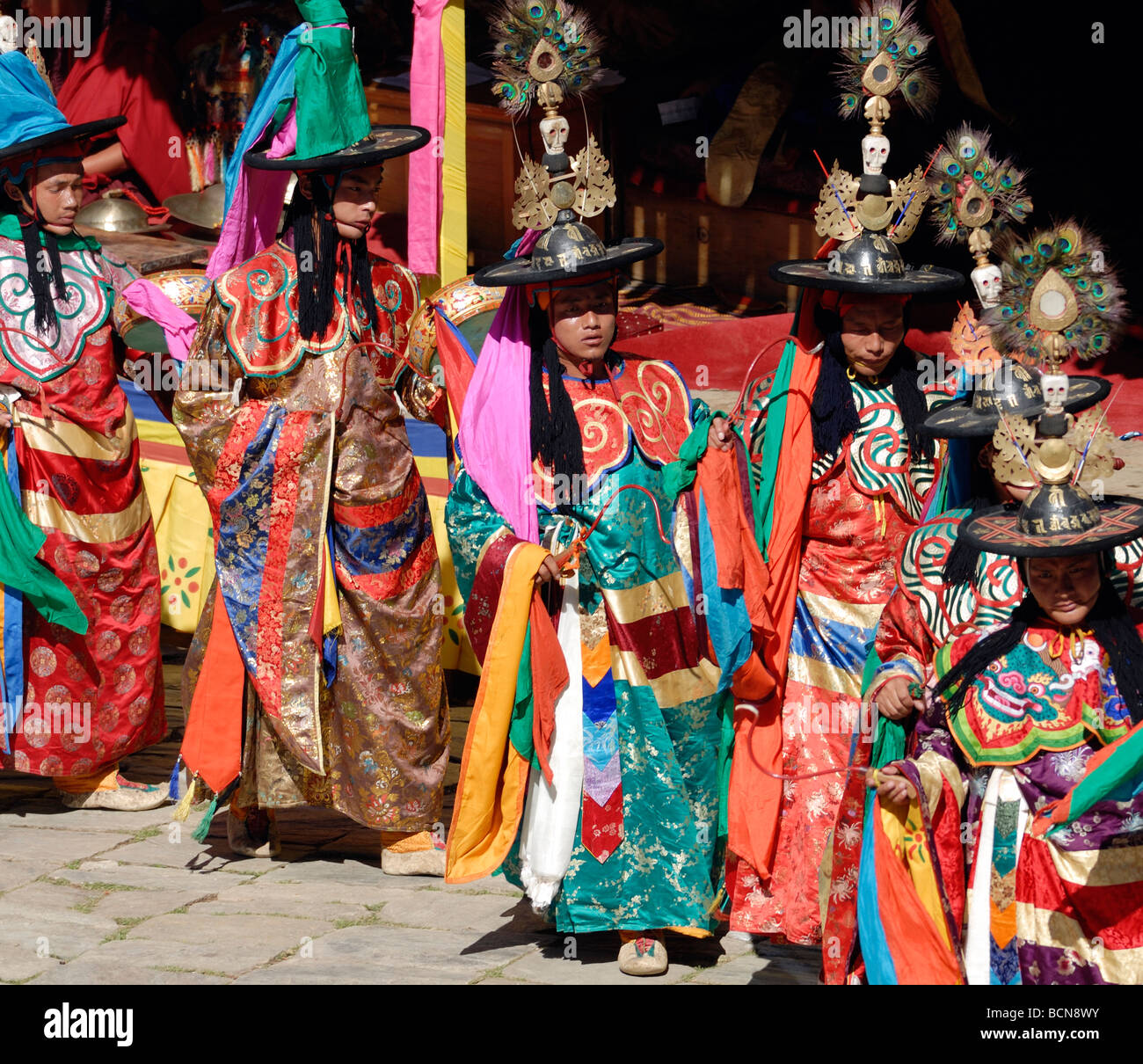 Black hat dancers dressed in gorgeous silk robes process across the courtyard of Mongar Dzong.Stock Photo