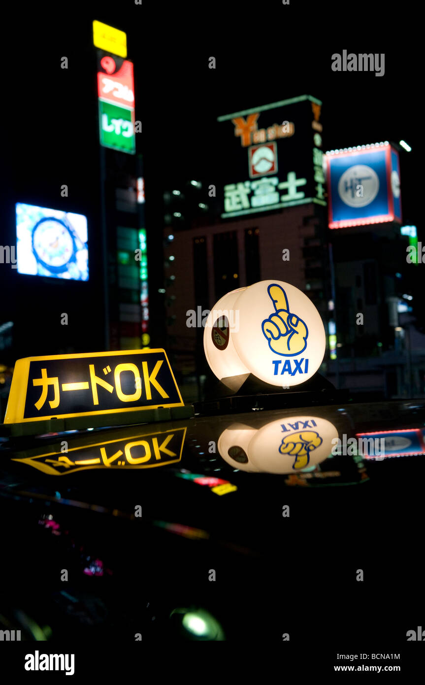 Illuminated taxicab toplight sign with neon lights and advertisement signs in Tokyo Japan - Stock Image