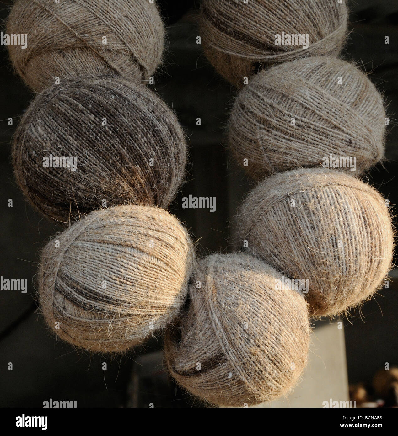 Balls of undyed naturally coloured wool hang in a village house. Nimaj, Rajasthan, Republic of India. Stock Photo