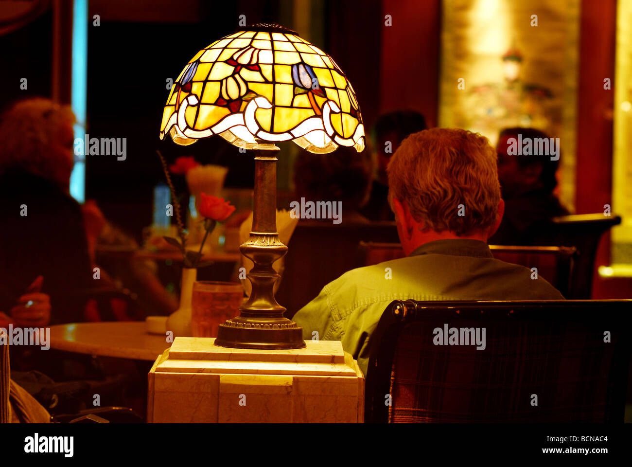 Foreign tourist resting in richly decorated café with stain glass lamp, Shanghai, China - Stock Image