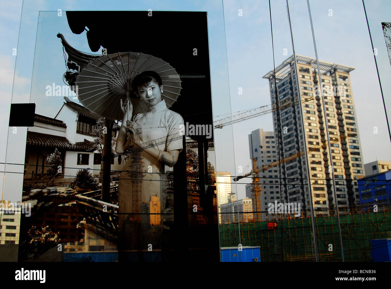 Black and white photograph of young woman in traditional Qipao against modern highrises, Shanghai, China - Stock Image