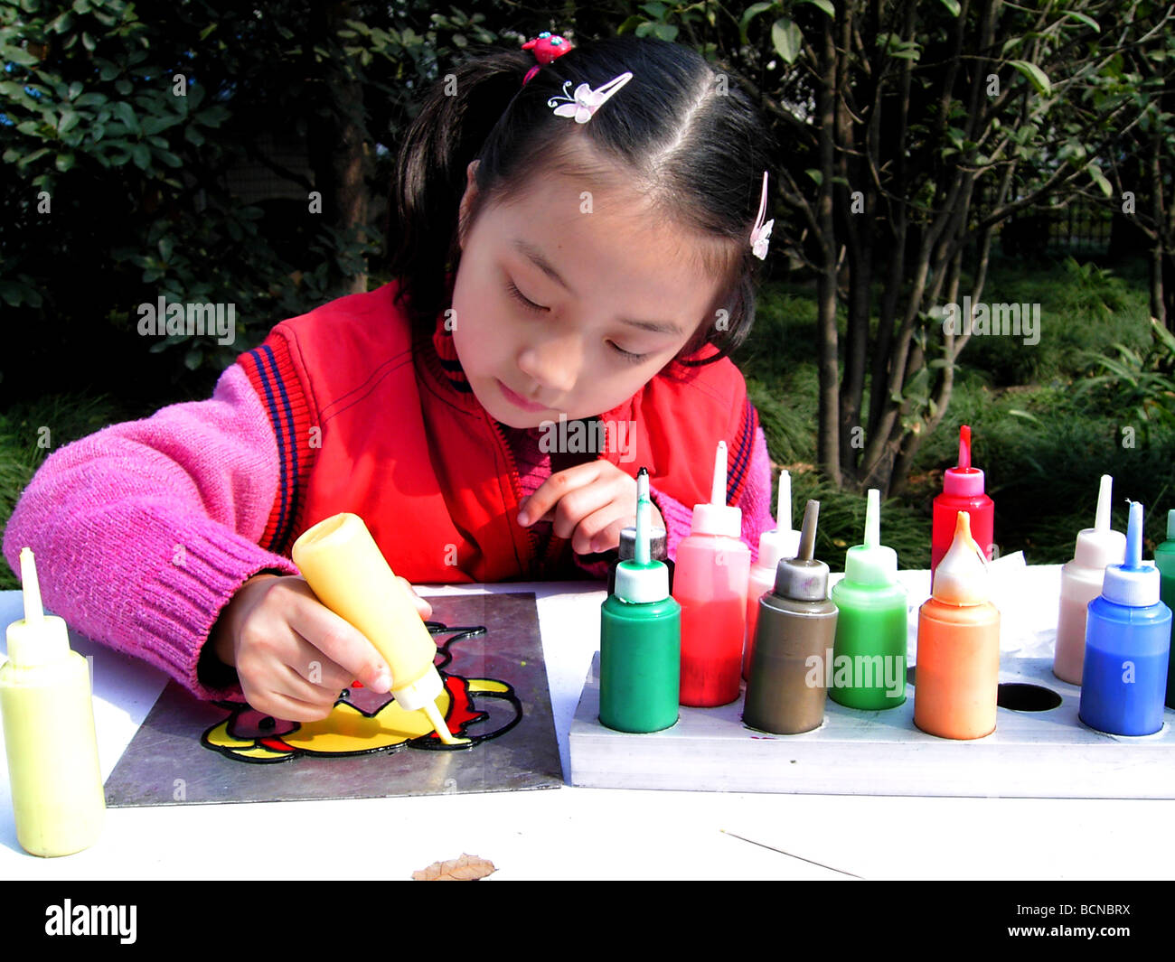 Chinese girl creating tempera painting, Shanghai, China - Stock Image
