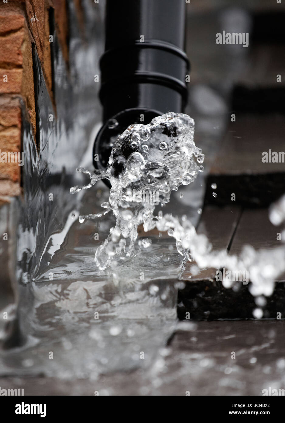 Rain water gushing from a drainpipe at a house in Worcestershire, UK - Stock Image