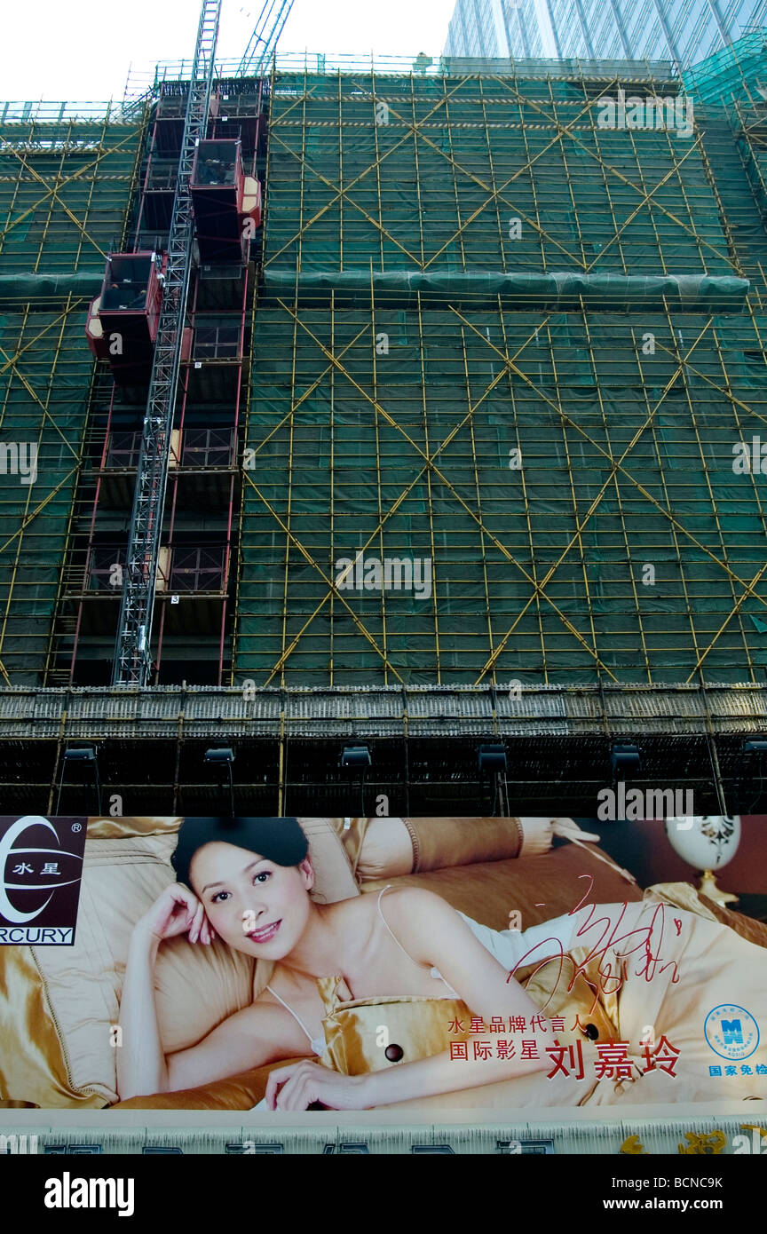 Renovating building with scaffold behind large outdoor advertisement, Nanjing Road, Shanghai, China - Stock Image