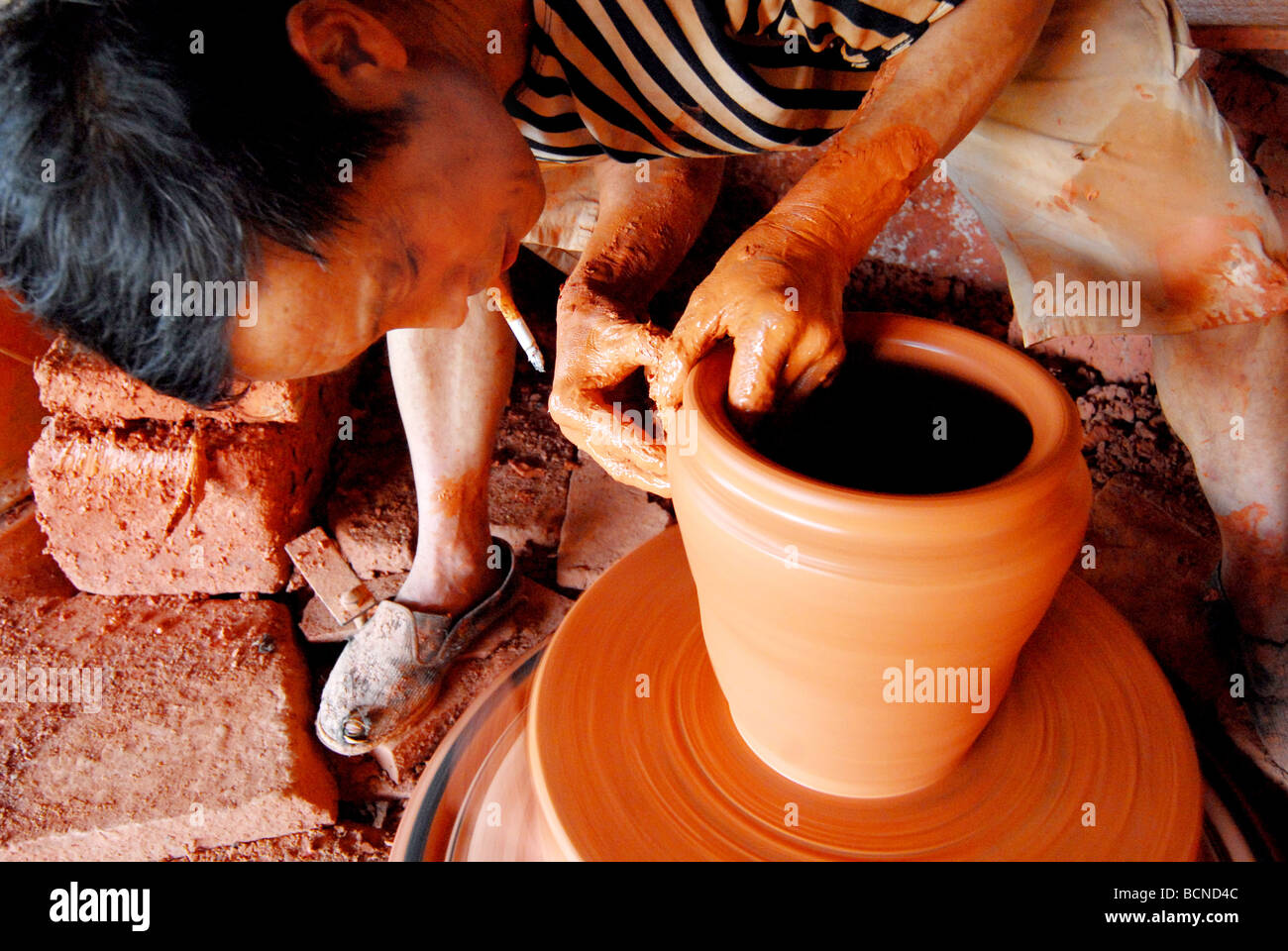 Chinese man making clay pots using century old technique in a kiln, Shuangliu, Szechwan Province, China - Stock Image