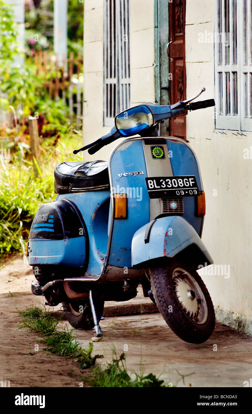 Blue Vespa motor scooter parked beside a wal - Stock Image
