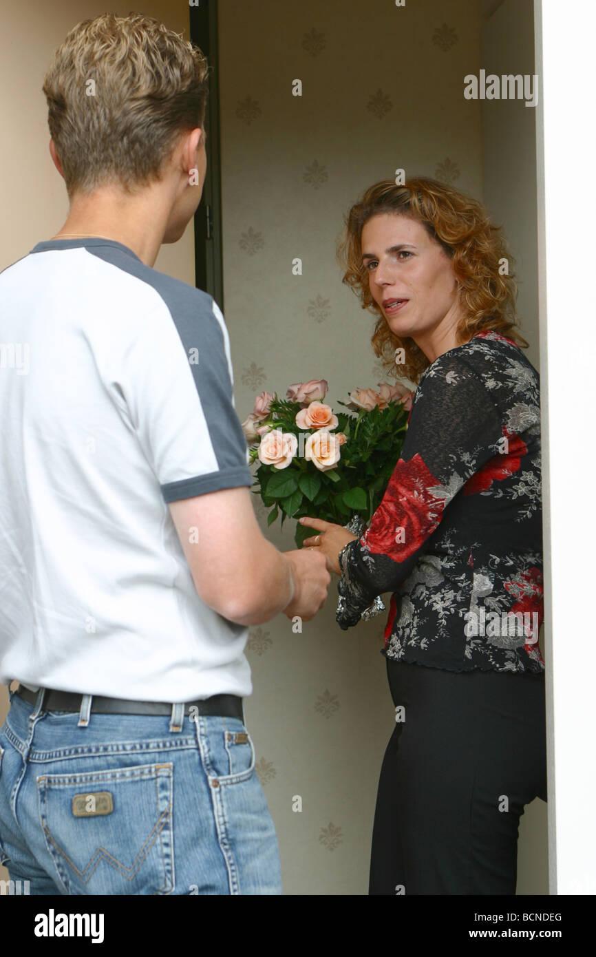 Man visiting woman and woman refusing advances - Stock Image