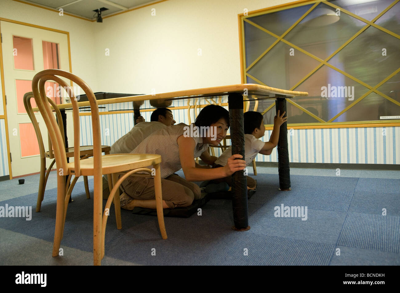 A Japanese family experience a computer-controlled earthquake at the Tokyo Earthquake Simulation Center of Ikebukuro - Stock Image