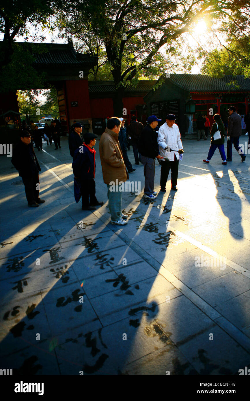 Onlookers observe the work of people practicing calligraphy using brush and water, Beihai Park, Beijing, China - Stock Image