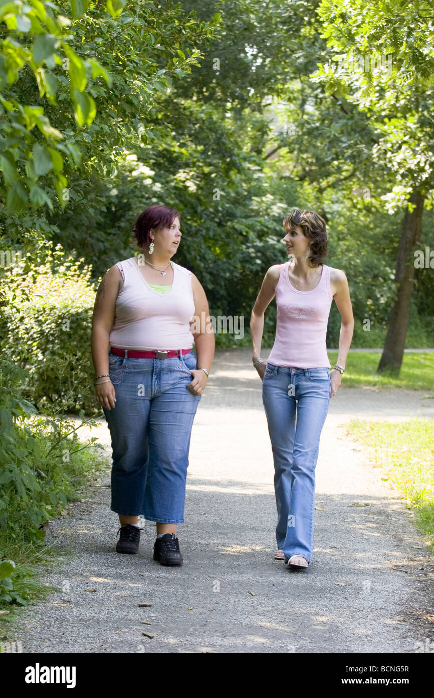 Plus sized woman and slim woman talking and having physical exercise outside in park by walking. Seriecvs617001 - Stock Image