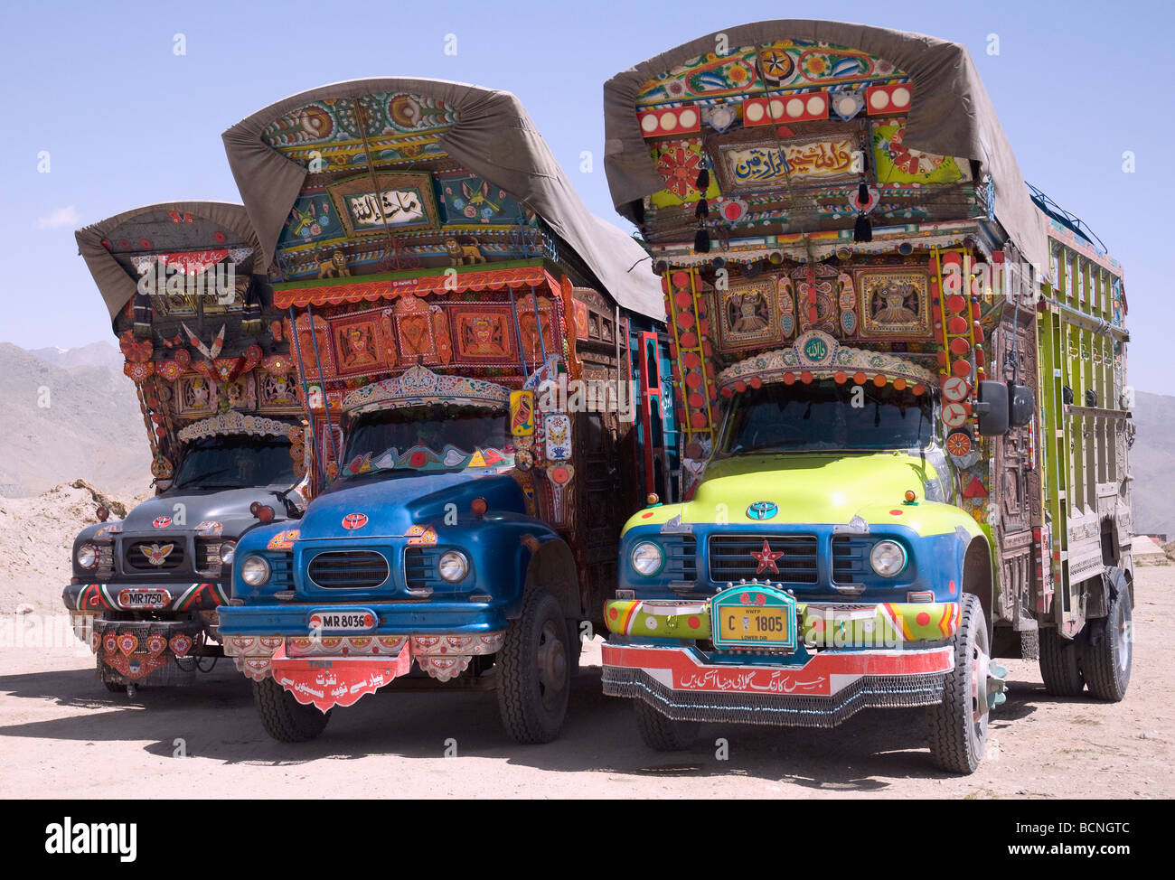 Three elaborately decorated Pakistani trucks parked beside the main road north of Kabul, Afghanistan - Stock Image